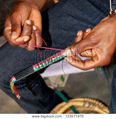 Accra. Ghana - October 5 2013: The craftsman weaves a decoration from colorful threads (close-up). Indigenous cultures in developing countries.