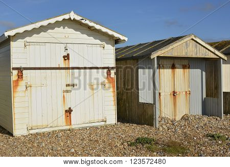 Wooden beach huts on shingle beach at Lancing Near Brighton West Sussex England
