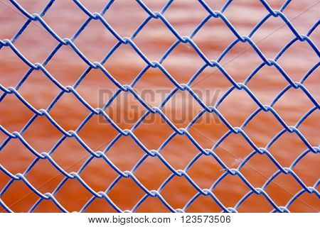 The grid above the red water. The texture of the lattice. Latticed ceiling near the water. Iron fence outside.