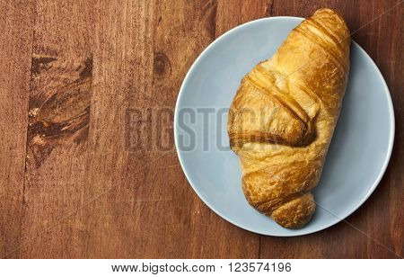 A photo of a croissant on a blue plate on a wooden board texture shot from above with a place for text