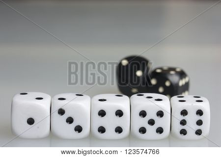 Dice. Playing cubes. Throwing the dice during the game. White cubes arranged in a row. Black cubes located behind them.