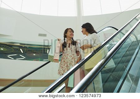 Vietnamese mother ands daughter going down the escalator after shopping