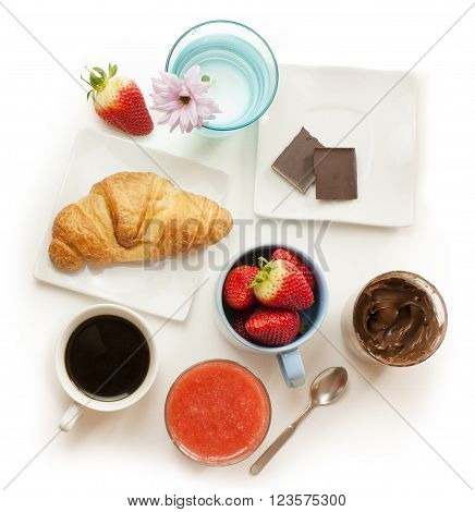 A healthy breakfast: a cup of coffee fresh strawberries a croissant a strawberry smoothie chocolate spread two ounces of dark chocolate with a tender pink chrysanthemum shot from above on white