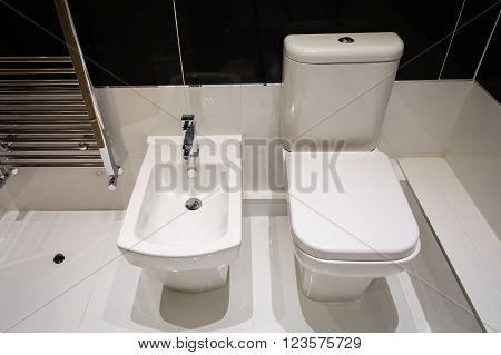 White Bidet and Toilet in a coordinated modern bathroom