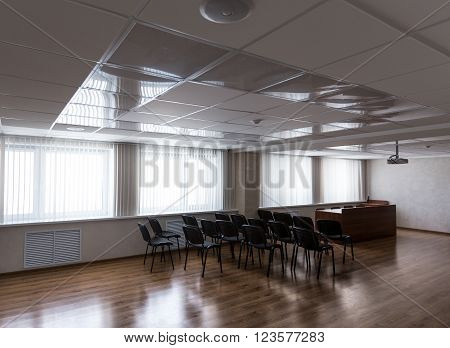 Empty sunlit modern meeting room with projector hanging on ceiling and black chairs standing in rows horizontal view