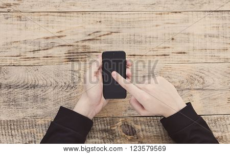 Close up of male hands holding smartphone and pointing finger to graph and text on screen at table wooden planks. Hipster style.