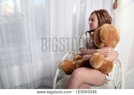 woman with a plush bear sitting in a shirt on a vintage chair near the window