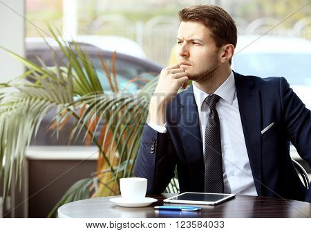 Portrait of handsome successful man drink coffee and look to the digital tablet screen sitting in coffee shop, business man having breakfast