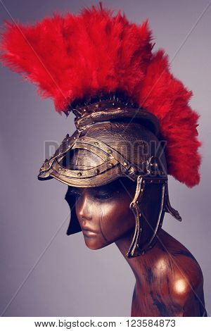 Mannequin in helmet with red feathers on grey background