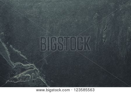 Vintage toned grunge background or texture made of cracked dark slate.
