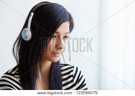 Portrait Of Support Female Phone Operator With Headset, Looking Down