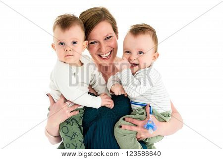 Mother is carrying twin boys and smiling. Happy family with twins and happy mother.