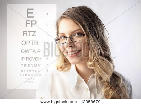 Smiling eye specialist with ophthalmic table on the background