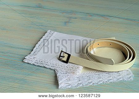 The strap and two handkerchiefs on a blue wooden background.
