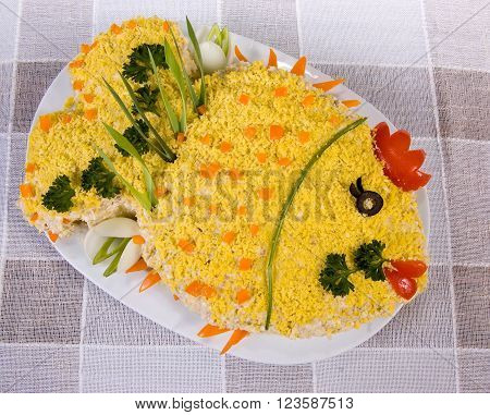 Fish salad in the shape of a fish, with boiled eggs and greenery on tablecloth