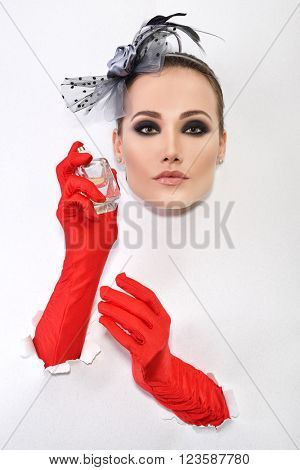 Retro fashion portrait of young woman with red gloves and bottle of perfume.