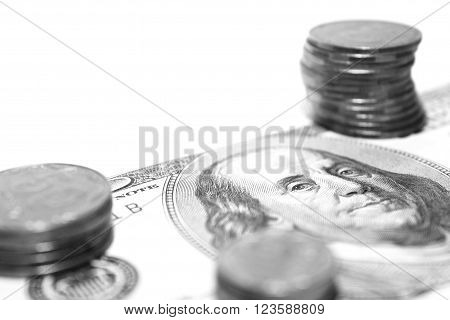 Stack of silver coins on on dollar bill close-up, black and white photo