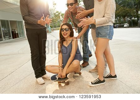 Pretty girl sitting on skateboard and her friends standing around