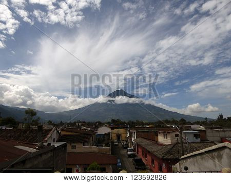 An overview of the colonial city of Antigua Guatemala with the Agua volcano visible on the horizon.