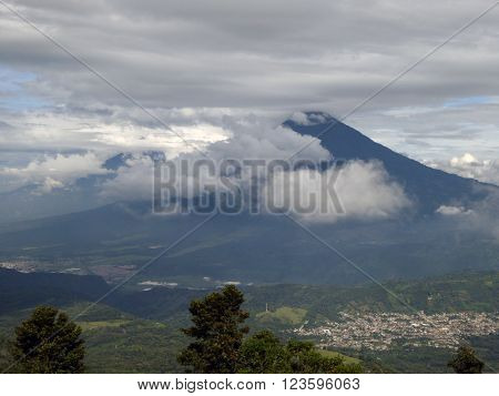 A view of clouds pushing up the Acatenango volcano and its surroundings including a small city taken from the adjacent Pacaya volcano in Guatemala.