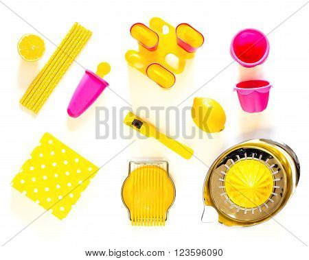 Pink and yellow kitchen utensils on a white table