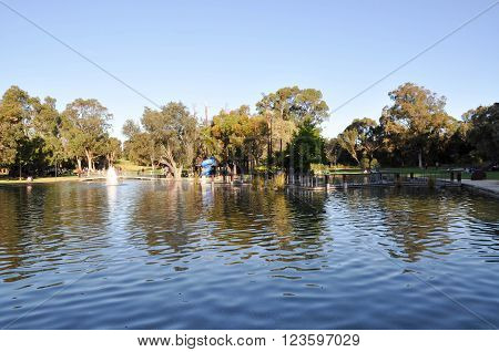 PERTH,WA,AUSTRALIA-AUGUST 22, 2015: Synergy Parkland with island playground and pond with tourists at King's Park botanical gardens in Perth, Western Australia.