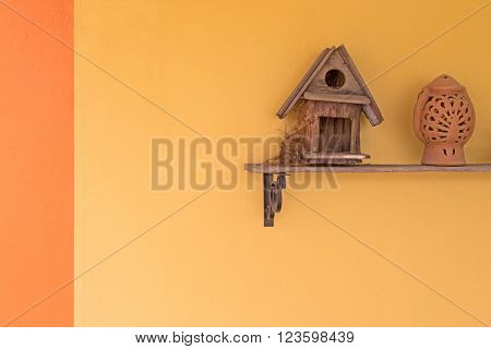 Oriental magpie robin bird build up its nest inside wooden bird house on a shelf against yellow wall