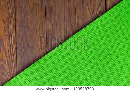 Detail of perforated green yoga mats on the wooden background. Texture yoga mats and boards. Boards brown. The diagonal orientation. The concept of a healthy lifestyle. Weight loss and fitness.