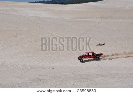 LANCELIN,WA,AUSTRALIA-SEPTEMBER 28,2015: Red dune buggy with checkered flag on the white sand dunes recreational attraction in Lancelin, Western Australia.