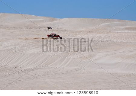 LANCELIN,WA,AUSTRALIA-SEPTEMBER 28,2015: Dune buggy with checkered flag on the white sand dunes under a blue sky in Lancelin, Western Australia.