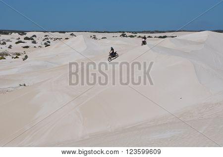 LANCELIN,WA,AUSTRALIA-SEPTEMBER 28,2015: Motorbike recreational vehicles racing the peaks of the white sand dunes in Lancelin, Western Australia.