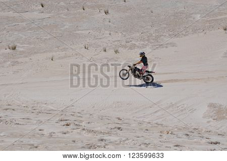 LANCELIN,WA,AUSTRALIA-SEPTEMBER 28,2015: Motorbike rider doing a wheelie on the white sand dunes in Lancelin, Western Australia.