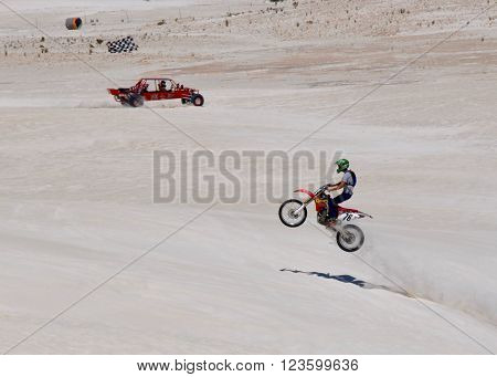 LANCELIN,WA,AUSTRALIA-SEPTEMBER 28,2015: Dune buggy and jumping motorbike rider at the white sand dunes recreational attraction in Lancelin, Western Australia.