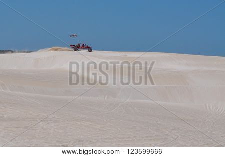 LANCELIN,WA,AUSTRALIA-SEPTEMBER 28,2015: Red dune buggy with checkered flag and driver racing across the pristine white sand dune landscape in Lancelin, Western Australia.