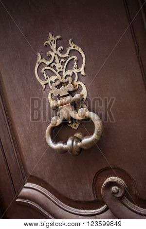 Weathered wrought iron knocker on a wooden door