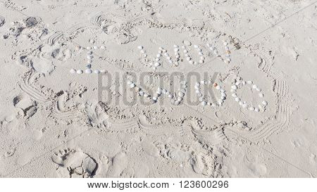 an inscription I wuv woo of small white shells and bright yellow sand fines with small stones and fragments of shells on the sandy beach
