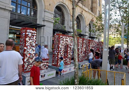 PERTH,WA,AUSTRALIA-FEBRUARY 14,2015: People attaching locks for donation to charity on large L,O,V, and E  red letters in the shopping district of Perth, Western Australia