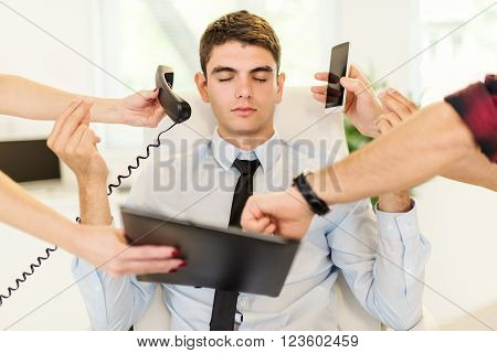 Young overworked businessman relaxing in the office. He sits on lotus pose and meditating. Around his it is bunch of work.