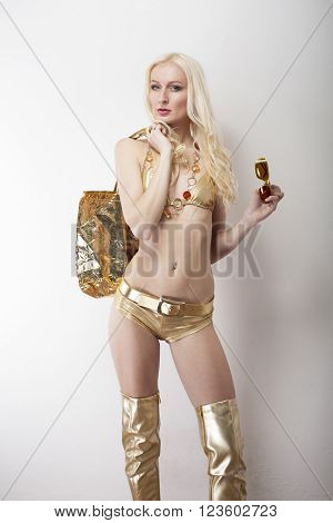 longhair blonde in golden bikini and tigh high heel boots and shopping bag