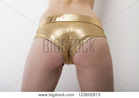 Woman shows sexy buttocks in golden hot pants capture from behind