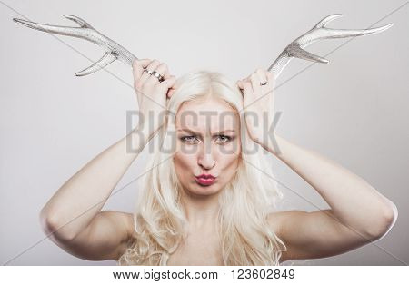Portrait of a blond woman holding deer antlers to her head making angry expression