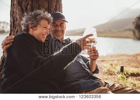 Senior Couple Drinking Wine At Campsite.
