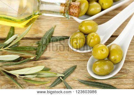 green olives and olive oil on wooden surface