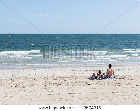unrecognizable young man and woman on the big pure sadness beach and beautiful blue sea and small waves with white foam and blue sky on a sunny day