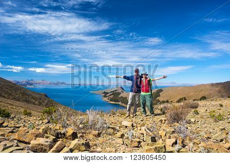 Couple of tourist with outstretched arms looking at camera on the Island of the Sun Titicaca Lake Bolivia. Concepts of wanderlust and people traveling around the world. Expansive view.