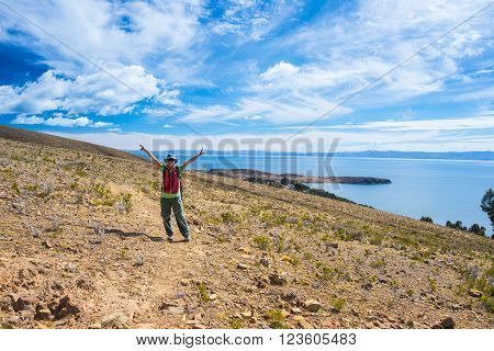 Tourist with outstretched arms on Inca trail at the Island of the Sun Titicaca Lake Bolivia. Concepts of wanderlust and people traveling around the world. Expansive view.