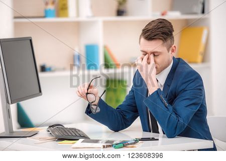 Young businessman with suit working in office. Businessman using computer and having headacke. Office interior with bookcase