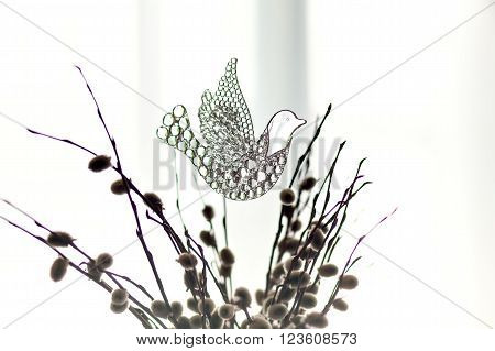 Souvenir glass dove, symbol of peace and spring. Figurine of a bird in flight dove clear of willow branches. A beautiful sign of spring. With copy space. Glass toy on the background of a window