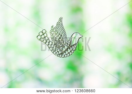 Souvenir glass dove, symbol of peace and spring. Figurine of a bird in flight Dove transparent. A beautiful sign of spring. With copy space. Glass toy on a background of green