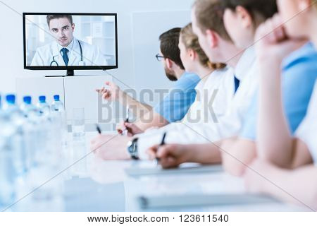 Medics in uniforms during video chat with young handsome doctor sitting in light office